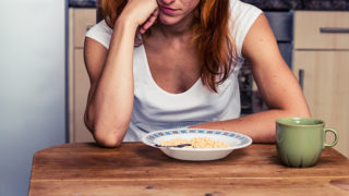 Young woman in her kitchen is dissapointed that she is having cereal for breakfast again