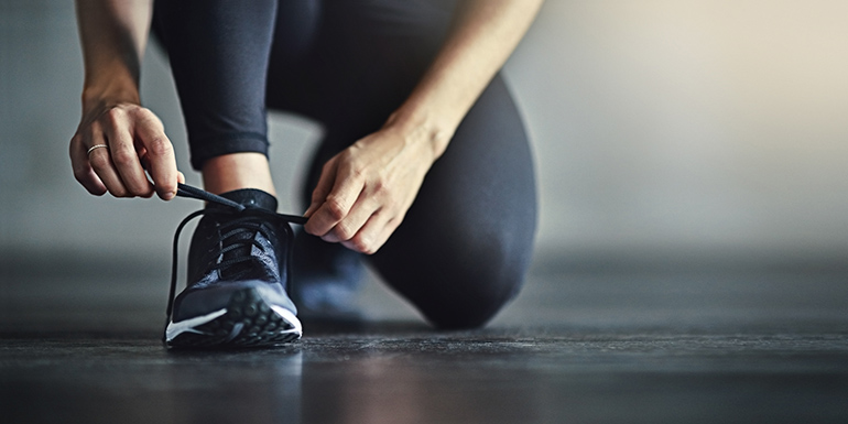 Cropped shot of a woman tying her shoelaces before a workout