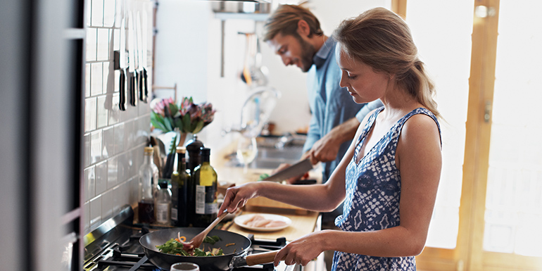 Shot of a young couple cooking together in the kitchen
